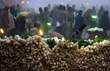 Radishes are seen piled up as customers wander at a wholesale vegetable market on a cold morning in Chandigarh January 10, 2011. REUTERS/Ajay Verma