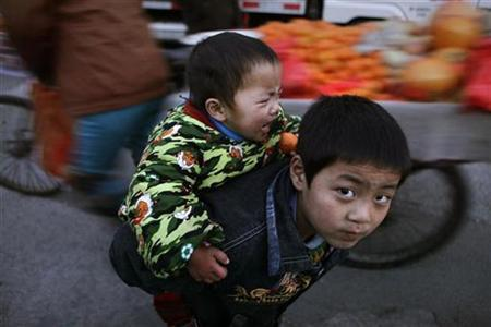 A boy carries his brother on his back at a residential area of migrant workers on the outskirts of Beijing, December 8, 2010. REUTERS/Jason Lee
