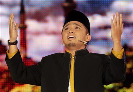 ''Young Imam'' contestant Asyraf sings during the Malaysian reality TV competition to find the country's best young Imam during its live telecast in Kuala Lumpur July 30, 2010.REUTERS/Bazuki Muhammad (MALAYSIA - Tags: SOCIETY RELIGION ENTERTAINMENT)