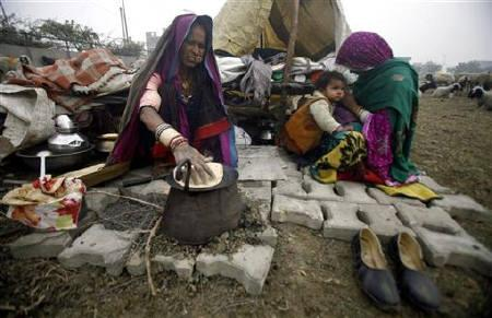 A nomad from Rajasthan prepares a ''roti'' (Indian bread) outside a makeshift tent on a cold morning at Parthla village, in Uttar Pradesh January 10, 2011. REUTERS/Parivartan Sharma