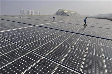 Technicians work on a roof covered with solar panels at a solar power plant in Wuhan, Hubei province, January 12, 2010. REUTERS/China Daily