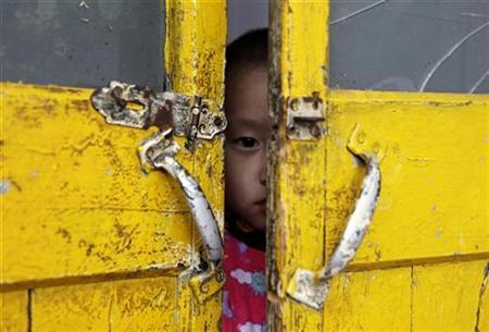 A three-year-old boy looks out from a door of a classroom in Tenglong kindergarten, a school for children of migrant workers, in Beijing December 2, 2010. REUTERS/Jason Lee