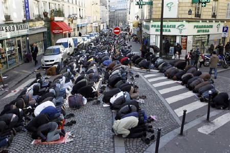 Muslims pray in the street during Friday prayers near the Poissonniers street Mosque in Paris December 17, 2010.  REUTERS/Charles Platiau/Files