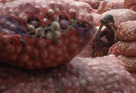 A labourer sits on a sack of onions as she takes a break at a wholesale market in Hyderabad February 11, 2010. REUTERS/Krishnendu Halder/Files