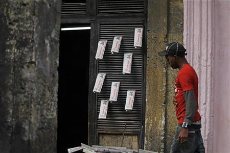 A youth walks beside copies of the official newspaper of the Cuban Communist Party (PCC) ''Granma'' for sale in Havana January 14, 2011. REUTERS/Desmond Boylan (CUBA - Tags: SOCIETY POLITICS)