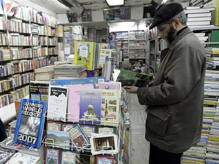 A man browses a book inside a bookstore in Srinagar December 9, 2006. REUTERS/Danish Ismail/Files