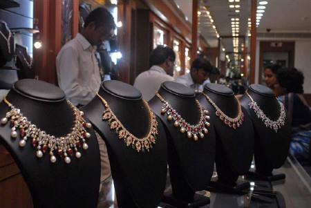 Salesmen at a jewellery shop attend to their customers in Hyderabad July 6, 2009. REUTERS/Krishnendu Halder/Files