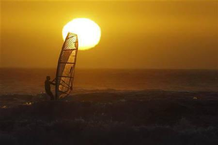 The Sun sets behind windsurfers at Blaauwberg beach in Cape Town January 17, 2011. REUTERS/Mike Hutchings