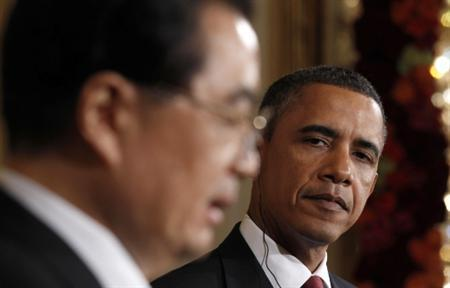 President Barack Obama (R) listens as Chinese President Hu Jintao speaks during a joint news conference at the White House in Washington January 19, 2011. REUTERS/Kevin Lamarque