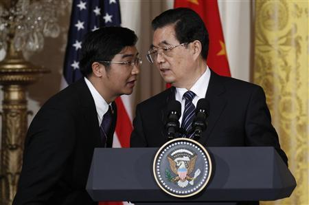 China's President Hu Jintao (R) has his translator repeat a question in Chinese, concerning human rights, during his joint news conference with U.S. President Barack Obama in the East Room of the White House in Washington, January 19, 2011. REUTERS/Jim Young