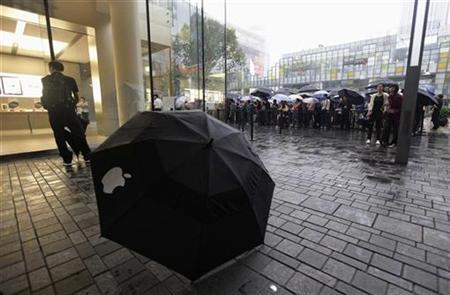 Customers queue to buy the iPad at an Apple flagship store on a rainy day in Beijing, September 17, 2010. REUTERS/Petar Kujundzic
