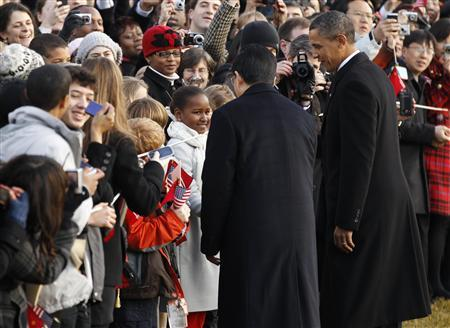 China's President Hu Jintao is introduced to nine-year-old Sasha Obama (C in white coat) by U.S. President Barack Obama as they greet the crowd during an official south lawn arrival ceremony for Hu at the White House in Washington January 19, 2011. REUTERS/Kevin Lamarque