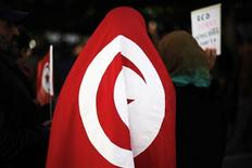 <p>A female protester wears a Tunisian flag in front of the Prime Minister's office during a demonstration in downtown Tunis, January 21, 2011. REUTERS/ Finbarr O'Reilly</p>