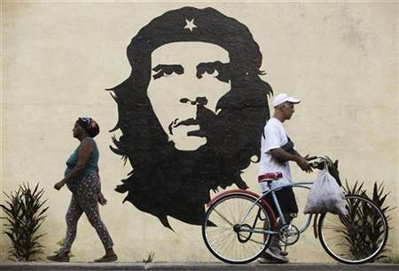 People walk in front of a mural with the image of revolutionary leader Che Guevara in San Jose de las Lajas, on the outskirts of Havana September 22, 2010. REUTERS/Enrique de la Osa