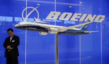 An exhibitor stands near a scale model of Boeing 787 Dreamliner passenger jet at the Singapore Airshow February 2, 2010. REUTERS/Tim Chong/Files