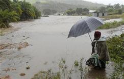 <p>Женщина идет по затопленной местности близ Дурбана, 18 июня 2008 года. Наводнения в ЮАР унесли жизни более 100 человек, нанесли ущерб фермерским хозяйствам страны и вынудили власти объявить чрезвычайное положение в 33 округах. REUTERS/Rogan Ward</p>