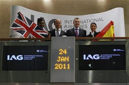 CEO of International Consolidated Airlines Group (IAG) Willie Walsh (2nd R) poses with IAG Chairman Antonio Vazquez (2nd L), next to a British flag and a Spanish flag, inside the Stock Exchange in London January 24, 2011. REUTERS/Stefan Wermuth