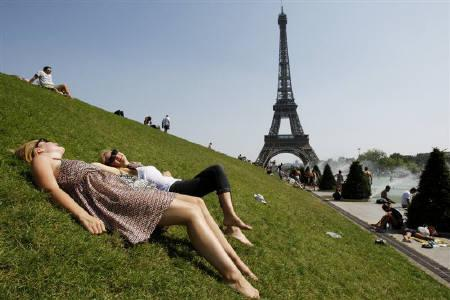 People sit on the grass and sunbathe near the Trocadero fountains across from the Eiffel Tower on a hot summer day in Paris August 19, 2009. REUTERS/Benoit Tessier/Files