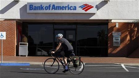 A bicyclist rides past a Bank of America in Tucson, Arizona January 21, 2011. Bank of America Corp, the largest U.S. bank, reported weaker-than-expected revenue and a second straight quarterly loss after its limping mortgage business triggered writedowns and legal settlements. REUTERS/Joshua Lott