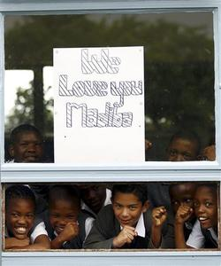 Schoolchildren from a school adjacent to Milpark hospital in Johannesburg show off a placard wishing former South African president Nelson Mandela a speedy recovery January 27, 2011. REUTERS/Siphiwe Sibeko