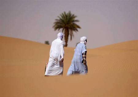 Men walk at Sidi Manssour on the outskirts of the oasis town of Timimoun about 1,200 km (146 miles) south of Algiers March 26,2008. REUTERS/Zohra Bensemra/Files
