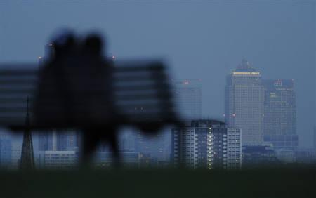 A couple embrace, as the Canary Wharf financial district is seen behind, in London January 22, 2009.   REUTERS/Toby Melville/Files