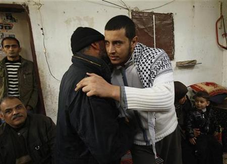 Army of Islam militant Hassan Wshah (R) is greeted by a relative upon his arrival to his home in al-Bureij refugee camp in the central Gaza Strip January 30, 2011, after fleeing Cairo's Abu Zaabal prison as it was raided on Saturday by an Egyptian mob amid spreading chaos in the Egyptian capital. REUTERS/Ibraheem Abu Mustafa