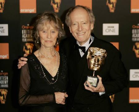 British composer John Barry (R) poses with his 'BAFTA Fellowship' award with British actress Virginia McKenna who presented the award at the BAFTA (British Academy of Film and Television Arts) awards at the Odeon Leicester Square cinema in London February 12, 2005. REUTERS/Matthew Dunham/Files