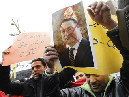 Egyptians living in South Korea hold up a poster Egypt's President Hosni Mubarak as they attend a rally demanding the end of his 30-year rule near the Egypt embassy in Seoul January 31, 2011. REUTERS/Lee Jae-Won