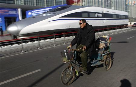A resident rides a tricycle past the head of a CRH (China Railway High-speed) Harmony bullet train outside an exhibition for the Seventh World Congress on High Speed Rail in Beijing December 7, 2010. REUTERS/Jason Lee