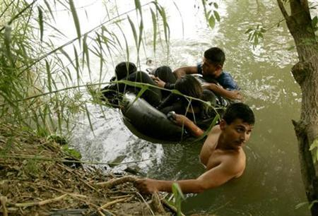 A group of illegal aliens wait on the U.S. side of the Rio Grande river, after floating across in a tire tube, in Laredo, Texas May 2, 2006. REUTERS/Rick Wilking