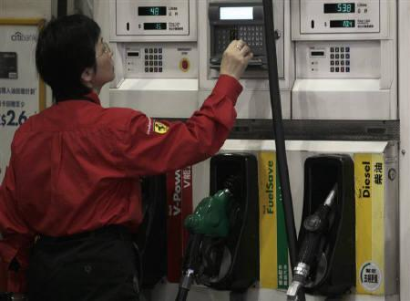 A worker checks the price of fuel at a gas station in Hong Kong January 14, 2011. REUTERS/Tyrone Siu/Files