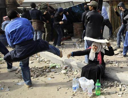 A woman opposition supporter takes shelter while providing water during rioting with pro-Mubarak demonstrators near Tahrir Square in Cairo February 3, 2011. REUTERS/Goran Tomasevic