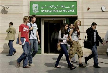 Tourists walk in front of National Bank of Abu Dhabi in downtown Cairo February 17, 2010. REUTERS/Tarek Mostafa/Files