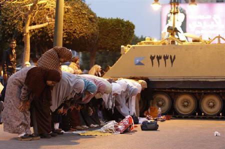Muslim women pray beside a tank during a break in mass demonstrations against Egypt's President Hosni Mubarak in Alexandria February 3, 2011. REUTERS/Dylan Martinez