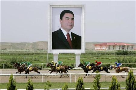 Horses race past a giant portrait of Turkmen President Kurbanguly Berdymukhamedov at the presidential race track in Ashgabat May 11, 2007. RETUERS/ITAR-TASS/PRESIDENTIAL PRESS SERVICE