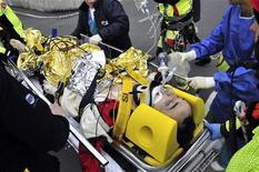 <p>Equipe de resgate ajuda piloto Robert Kubica após acidente em Gênova. O piloto de Fórmula 1 voltou a mexer os dedos nesta segunda-feira após o grave acidente sofrido em uma corrida de rali no fim de semana. 06/02/2010 REUTERS/Stringer</p>