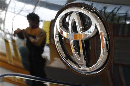 An employee is reflected on a Toyota Motor vehicle at the company showroom in Tokyo February 8, 2011. REUTERS/Toru Hanai