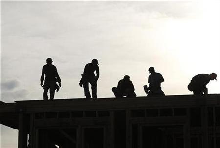 Workers are silhouetted as they stand on the roof of a building under construction in Los Angeles December 2, 2010. REUTERS/Mario Anzuoni