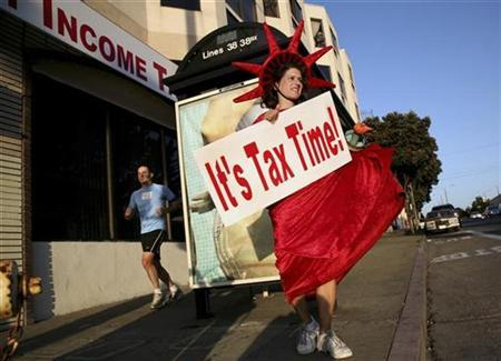 Denise Jameson wears a costume while carrying a sign to remind people passing on foot and in cars that it is income tax filing season outside a tax consulting business in San Francisco, California February 3, 2009. REUTERS/Robert Galbraith
