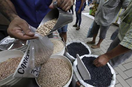 A vendor fills a bag of beans next to a customer at the Lapa Market in Sao Paulo January 20, 2011. REUTERS/Nacho Doce/Files