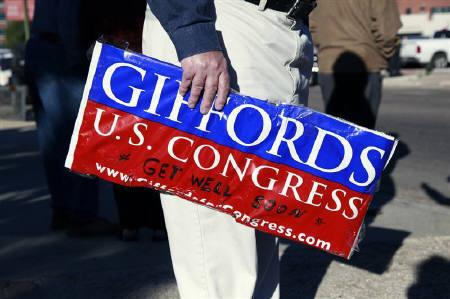 A spectator holds a campaign sign as he waits for the medial ambulance transporting U.S. Congresswoman Gabrielle Giffords to leave the University Medical Center en-route to Davis-Monthan Air Force Base in Tucson, Arizona January 21, 2011. REUTERS/Samantha Sais/Files