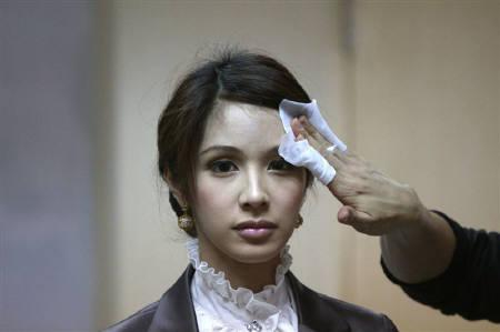 An instructor cleans the face of transsexual flight attendant Dissanai Chitpraphachin, 24, during a make-up training session at PC Air office in Bangkok February 9, 2011. REUTERS/Chaiwat Subprasom