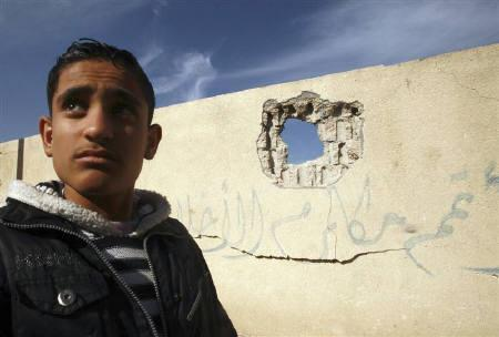 A Palestinian youth walks past a damaged wall after an Israeli air strike at a school in Gaza City December 9, 2010. REUTERS/Suhaib Salem/Files
