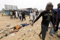 <p>People gather around a dead body in the neighbourhood of Abobo in Abidjan, January 11, 2011, after a clash between supporters of Ivory Coast's presidential claimant Alassane Ouattara and forces loyal to incumbent Laurent Gbagbo. REUTERS/Luc Gnago</p>