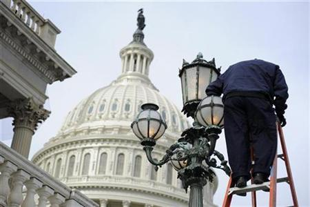 A worker replaces lightbulbs on the East Front of the U.S. Capitol, January 24, 2011. REUTERS/Jonathan Ernst