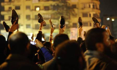 Anti-government protesters in Cairo's Tahrir Square wave shoes in dismay as President Hosni Mubarak speaks to the nation February 10, 2011. REUTERS/Dylan Martinez