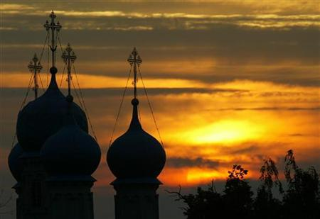 An orthodox cathedral is silhouetted as the sun sets in the village Zelyonaya Sloboda 50 km southeast from Moscow in this picture taken late on July 12, 2004. REUTERS/Viktor Korotayev