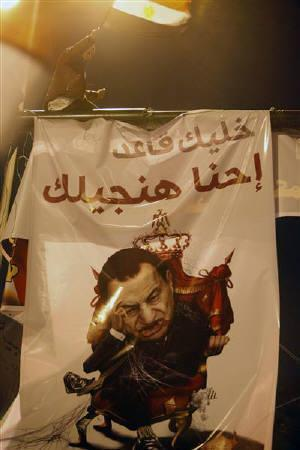 An anti-government protester celebrates atop a banner of President Hosni Mubarak inside Tahrir Square after the announcement of Mubarak's resignation in Cairo February 11, 2011. REUTERS/Asmaa Waguih