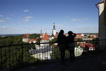 Tourists look at the view of the old city of Tallinn June 16, 2010. REUTERS/Ints Kalnins (ESTONIA - Tags: TRAVEL POLITICS)